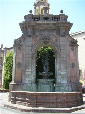 A fountain under an arch with a figure wielding a trident on top.
