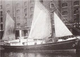 A ship with a black hull and white upper parts, three sails raised, in dock alongside a high multi-windowed warehouse building