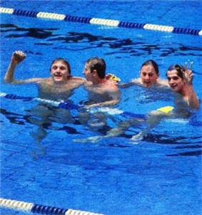 Four men in a pool celebrating