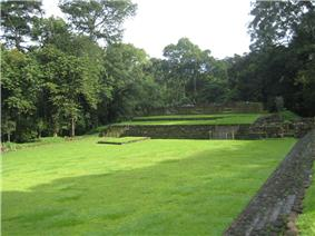 A flat grassy area with low stepped structures at the far side, bordered by trees