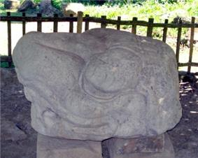 Stone sculpture shaped like the head of an animal looking to the left