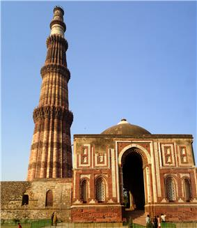 Red and white building with a white dome and a tall tower or minaret with varying cross sections depending on height.