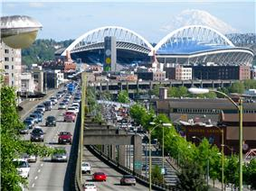 A stadium surrounded by historic buildings. A raised roadway runs along its side and a glacier capped mountain is behind it