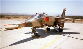 A Jaguar in desert camouflage scheme parked on hardstanding. The cockpit canopy is just open, with covers on the air intakes and on the nose probe, and a ladder giving access to the cockpit