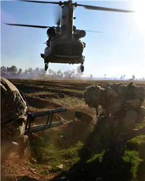 colour photograph of two marines in a field ducking as a low-flying helicopter fluies overhead.