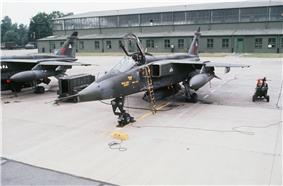 Two dark green jet aircraft (one partly obscured) parked on concrete ramp in front of building.