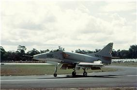 Colour photograph of a white military jet fighter taxiing along a runway