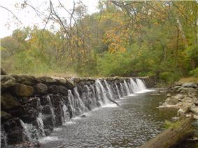 Several streams of water fall over a dam made of large rocks under autumn leaves