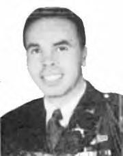 Head of a smiling young man with dark hair wearing a military jacket with pins on the lapel over a shirt and tie.