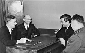 Four men sit facing each other around a table. Three of the men wear civilian suits, while one wears a military uniform
