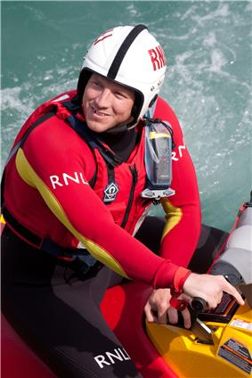 RNLI crewman seated in small inflatable, wearing helmet and bright red wetsuit.