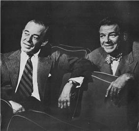 Two men in business suits sit in theatre seats amiably discussing what they are watching