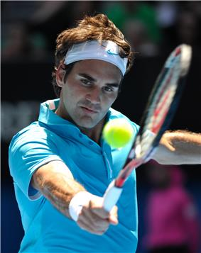 A brown-haired man in a light blue polo shirt and both white wristband and bandanna with a light blue nike logo, who is hitting a backhand with the tennis ball in the foreground