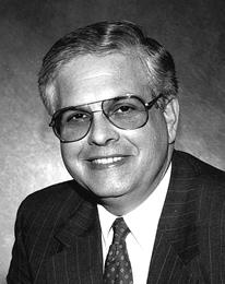The head and shoulders of a smiling clean-shaven man with graying hair, wearing tinted aviator-style glasses, and a tie and suit jacket with pin-stripes