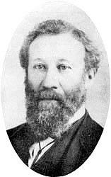 The head of a man with a long curly full beard, his hair parted on his left
