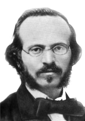 The head of a man with a large forehead and receding hair, a mustache and soul patch, and long thick sideburns, wearing small wire-rimmed glasses and a dark bow-tie