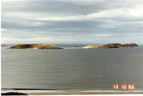 Two green sun-lit islets connected by a sandy tombolo sit offshore from a beach. The skies are grey and the sea all but flat calm.