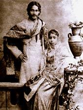 Black-and-white photograph of a finely dressed man and woman: the man, smiling, stands akimbo behind a settle with a shawl draped over his shoulders and in Bengali formal wear. The woman, seated on the settle, is in elaborate dress and shawl; she leans against a carved table supporting a vase and flowing leaves.