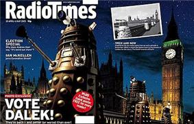 A gatefold magazine cover, depicting a nighttime scene with four gold Daleks in the foreground, the railing of a bridge in the midground, and the Perpendicular Gothic towers of the Houses of Parliament and Big Ben in the background. The left half of the image contains the text