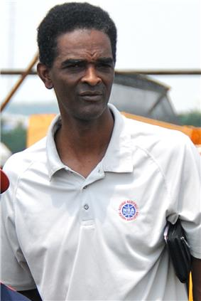 A man, wearing white shirt with a logo and the word