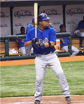 A man in a blue baseball jersey and white pants enters a right-handed batting stance.