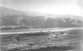 Historic photograph of Ranco Camulos from an elevated angle. The ranch spreads out on the valley bottom on the banks of a river, with mountains rising behind.