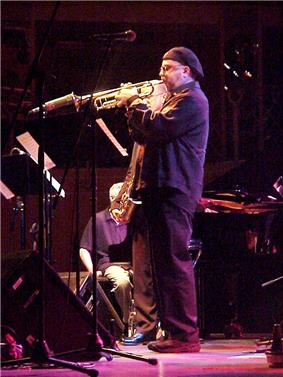 A man on a stage wearing all black and a cap on his head, playing a trumpet into a microphone. Behind him is a man holding a saxophone and another man sitting in a chair. Music stands and additional microphone stands are on the stage in front of them.