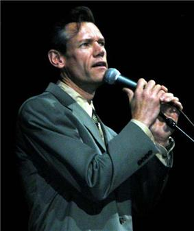 A man in a black suit clutching a microphone