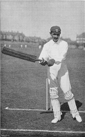 A cricketer about to hit the ball.