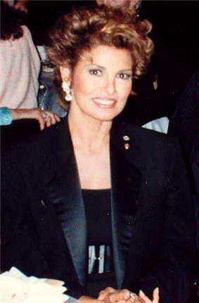 Welch in a dark scoop top, wide belt, and tuxedo-styled jacket, hair styled up
