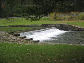 White water spills over a stone dam in a grassy setting with a highway guardrail in the background