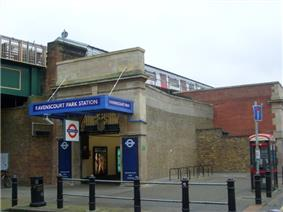 A brown-bricked building with a rectangular, dark blue sign reading