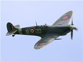 A Spitfire with RAF markings, flying against a blue sky