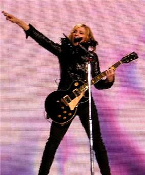 Woman wearing a black outfit while singing and playing a guitar.