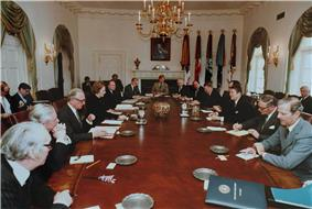 Thatcher is the only woman in a room, where a dozen men in suits sit around an oval table. Regan and Thatcher sit opposite each other in the middle of the long axis of the table. The room is which is decorated in white, with drapes, a gold chandelier and a portrait of Lincoln.