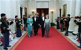 The Reagans and the Clintons walking a red carpet