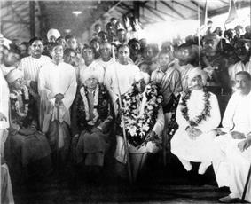 A group of people seated with garlands around the necks of some.