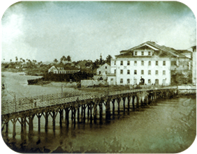 Photograph of a long wooden bridge crossing a river to a town with multi-storey white buildings and palm trees in the far background