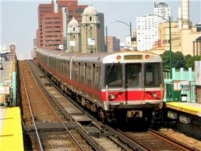 A silver and red rapid transit train entering an above-ground station