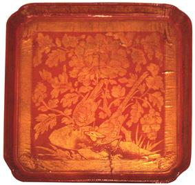 A red, square tray with cut off corners. Inlaid into the tray in gold foil is a design depicting two birds perched on a branch of a large, lowering plant.