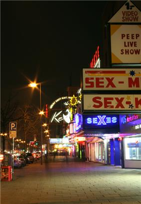 The Reeperbahn nighclub as seen from the side walk with its entrance lighted. Theatre marques say