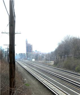 Four parallel railroad tracks on the Long Island Rail Road's Main Line in Rego Park, New York. Two outer trackways can clearly be seen, and run parallel to the four railroad tracks.