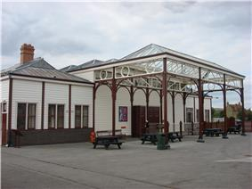 Large white wooden building with a large glass canopy