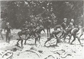 Black and white print of an oil painting by Frederic Remington shows slouch-hatted soldiers advancing in a crouch while crossing a stream