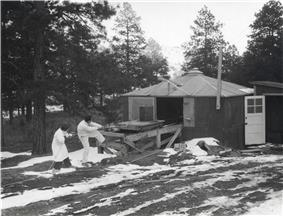 A shack surrounded by pine trees. There is snow on the ground. A man and a woman in white lab coats are pulling on a rope, which is attached to a small trolley on a wooden platform. On top of the trolley is a large cylindrical object.