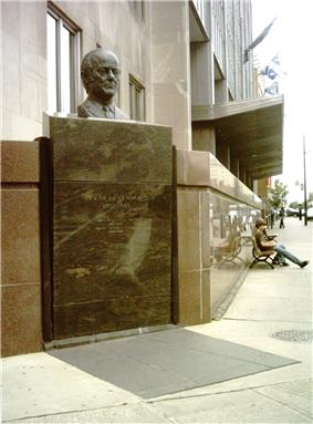 Bronze bust of a head and a plaque at a downtown street corner