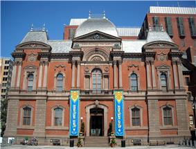 A 3 story, brick and red stone, second empire style building with a slate roof. The building is symmetrical with the entrance center and a blue and yellow banner on either side.
