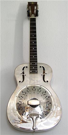 A metal guitar lies flat on its back, vertically aligned and on top of a grey background.