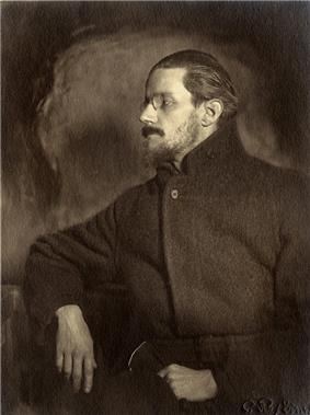 Half-length portrait of man in his thirties. He looks to his right so that his face is in profile. He has a mustache, a thin beard, and medium-length hair slicked back, and wears a pince-nez and a plain dark greatcoat, looking vaguely like a Russian revolutionary.