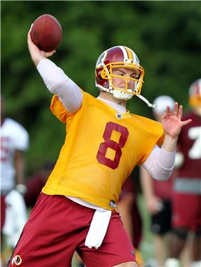 Grossman, in yellow non-contact practice jersey, throws a football in a Washington Redskins practice.